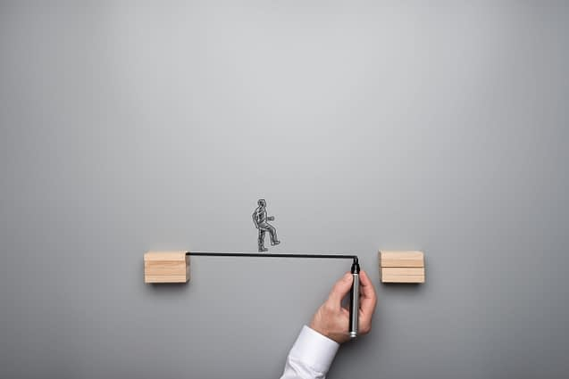 Business teamwork and strategy concept - male hand drawing a bridge between two wooden cubes with hand drawn businessman walking across.